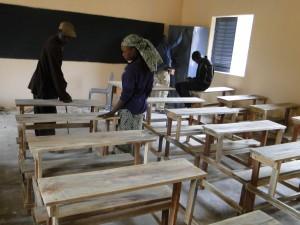 Le directeur de Kalagué et une enseignante devant les tables-bancs dans la nouvelle classe