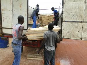 Chargement des planchers dans le camion pour confection de tables-bancs à Dogoro