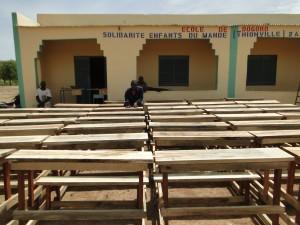 Montage des tables-bancs devant les nouvelles classes de Dogoro fincées par SEM